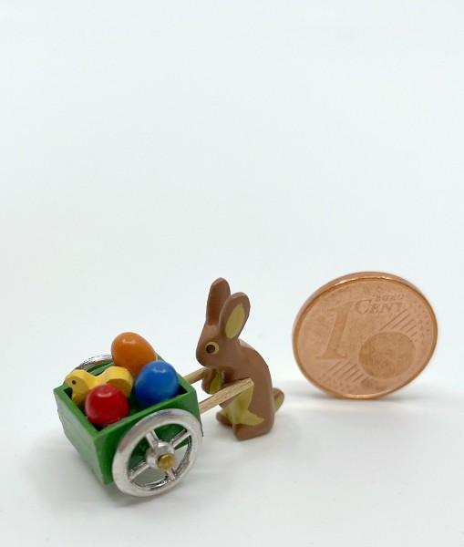 Miniaturhase mit grüner Eierkarre und Küken
