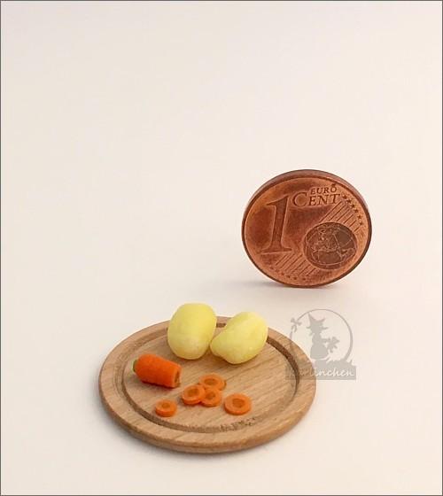 Holzbrettchen mit Möhren und Kartoffeln