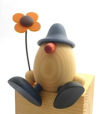 Anton mit Blume, auf Kante sitzend